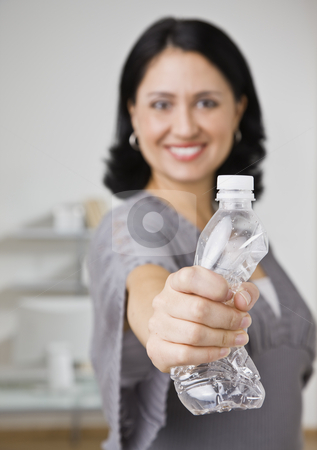 Woman in Office stock photo, A young businesswoman is standing in an office, holding a squished water bottle, and smiling at the camera.  Vertically framed shot. by Jonathan Ross