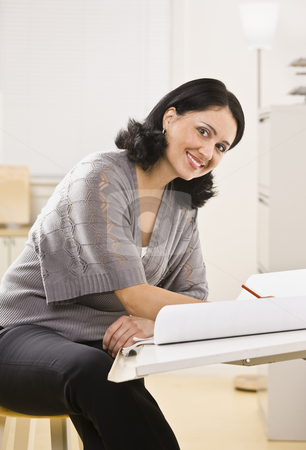 Attractive brunette woman drawing. stock photo, Attractive brunette woman drawing on white paper on board, smiling at camera. Vertical by Jonathan Ross