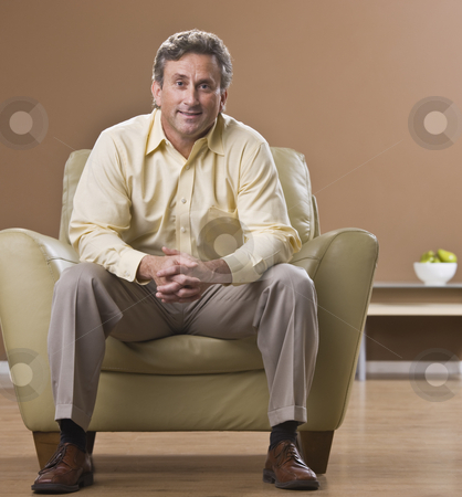 Man Sitting in Living Room stock photo, An older man is sitting in a chair in his living room and smiling at the camera.  Square framed shot. by Jonathan Ross