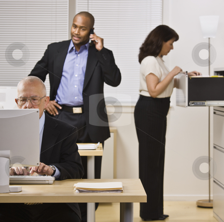 Business People Working in Office stock photo, Two businessmen and woman are working in an office.  The elderly man is on a computer, the younger man is talking on a cell phone and the woman in looking through a filing cabinet drawer.  Square framed shot. by Jonathan Ross