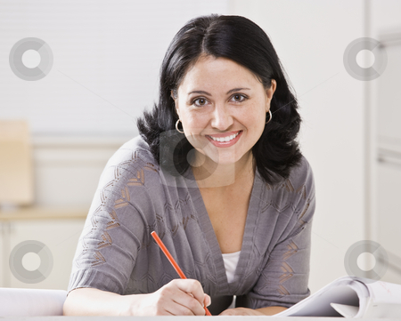 Beautiful Hispanic Woman Writing stock photo, A beautiful Hispanic woman writing at a desk.  She is smiling at the camera.  Square compostion. by Jonathan Ross