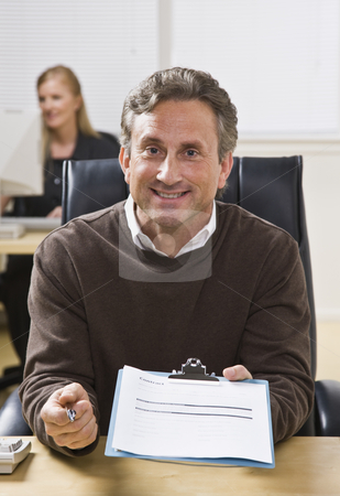 Man Holding Clipboard stock photo, A businessman is holding a clipboard out in front of him and is smiling at the camera.  There is a woman in the background.  Vertically framed shot. by Jonathan Ross