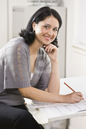 Woman Working on Paperwork stock photo, A young, attractive woman is looking over some paperwork on a desk, and smiling at the camera.  Vertically framed shot. by Jonathan Ross