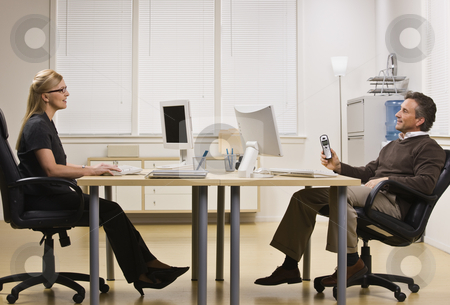 Man and Woman Chatting in Office stock photo, A businessman and woman are sitting across from each other at a desk in an office.  They are chatting with each other and looking away from the camera.  Horizontally framed shot. by Jonathan Ross