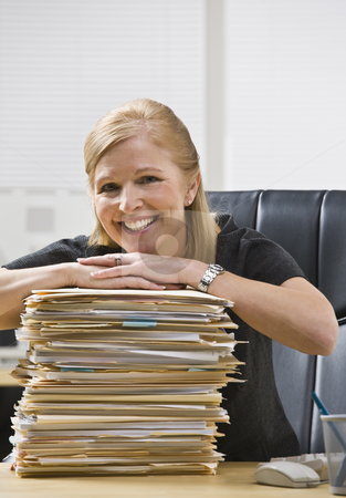 Woman in Office with Paperwork stock photo, A businesswoman is seated at a desk in an office with a stack of paperwork.  She is smiling at the camera.  Vertically by Jonathan Ross