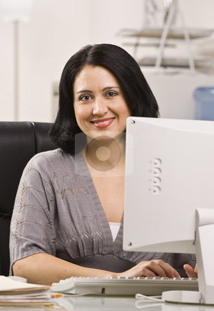 Attractive woman at desk. stock photo, Attractive woman sitting at desk behind monitor typing on keyboard. Vertical by Jonathan Ross