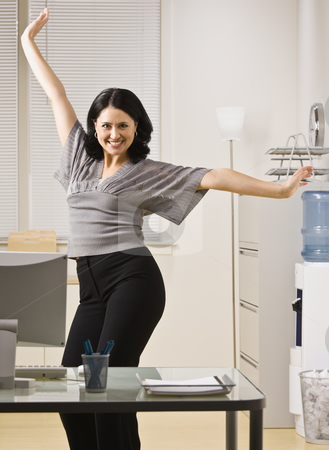 Woman Posing in Office stock photo, A young woman is standing in an office and striking a pose.  She is smilling at the camera.  Vertically framed shot. by Jonathan Ross