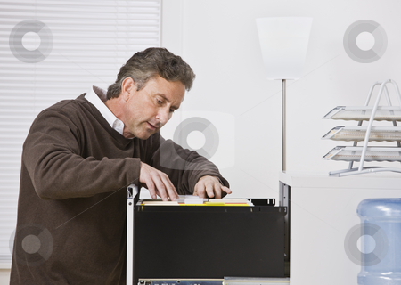 Attractive male looking for file. stock photo, Attractive male wearing a sweater in office, looking for file in filing cabinet. Looking away from camera. Horizontal. by Jonathan Ross