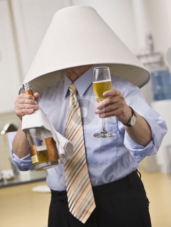 Male with Champagne Wearing a Lampshade stock photo, Male wearing lampshade on his head, holding Champagne bottle and glass in hands. Vertical by Jonathan Ross