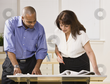 Man and Woman Working in Office stock photo, A businessman and woman are working together in an office.  They are looking away from the camera.  Horizontally framed shot. by Jonathan Ross