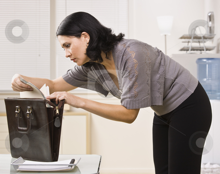 Woman Looking at File stock photo, A young businesswoman is standing over a briefcase and looking at a file.  Horizontally framed shot. by Jonathan Ross