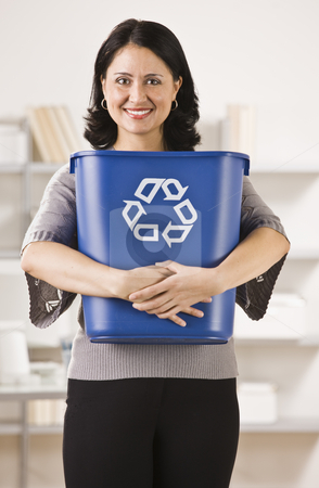 Woman Holding Recycling Basket stock photo, A businesswoman is holding a recycling basket and smiling at the camera.  Vertically framed shot. by Jonathan Ross
