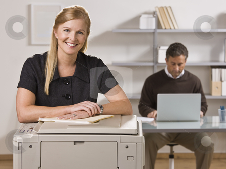 Man and Woman Working in Office stock photo, A businessman and woman are working in an office.  The man is working on a laptop and the woman is smiling at the camera.  Horizontally framed shot. by Jonathan Ross