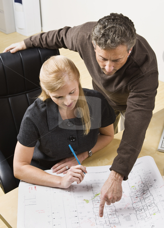 Man and Woman Working in Office stock photo, A man and a woman are working together on some blueprints in an office.  Vertically framed shot. by Jonathan Ross