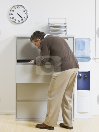 Man Looking Through Drawer stock photo, A businessman is looking through a drawer at an office.  Vertically framed shot. by Jonathan Ross