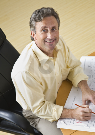 Man Working on Blueprints stock photo, A businessman is working on blueprints in an office.  He is smiling at the camera.  Vertically framed shot. by Jonathan Ross