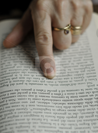 Reading a book stock photo, The hand of a mature woman pointing the words on the page while reading by Alessandro Rizzolli