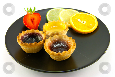 Jam tarts on a Black Plate stock photo, Red and yellow small jam tarts with slices of lemon, lime, orange and strawberry on a black plate on a white background by Keith Wilson