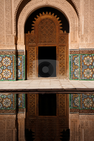 Ancient moroccan door and mosaic reflected in outdoor pool  stock photo, Ancient moroccan door and mosaic reflected in outdoor pool. Inside the Koranic school of Marrakech, Morocco by Wouter Roesems