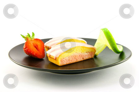 Strawberry Slices on a Black Plate stock photo, Two pink strawberry sliced cakes with icing on the top with a half strawberry and twist of lime on a black plate on a white background by Keith Wilson