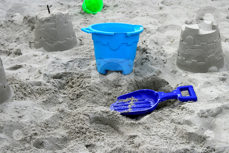 Bucket and Spade stock photo, Blue bucket and spade on the sand with constructed sandcastles and green bucket in the background by Keith Wilson