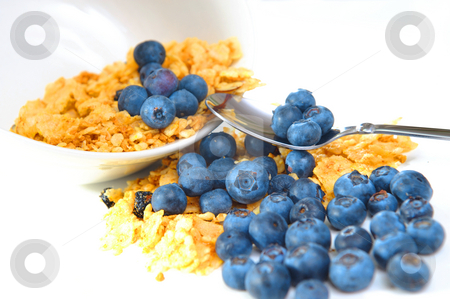 Cereal And Blueberries stock photo, A tipped bowl of cereal and blueberries on a light background with spoon holding a few berries. by Lynn Bendickson