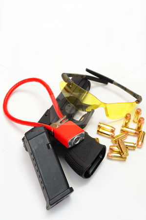 Gun, Cartridges  And Safety Accessories stock photo, A semi automatic pistol with a 10 round magazine, brass cartridges, amber colored protective eye-ware and a cable lock to secure the weapon when not in use. by Lynn Bendickson