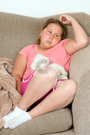 Bored Child stock photo, A bored child is sitting on a sofa with nothing to do by Richard Nelson