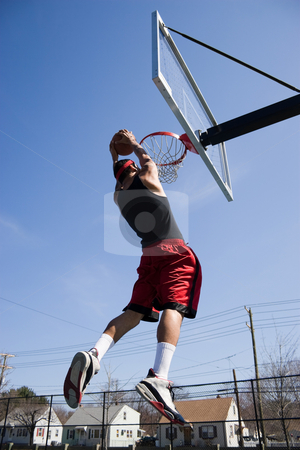 Man Dunking the Basketball stock photo, A young basketball player driving to the hoop for a slam dunk. by Todd Arena