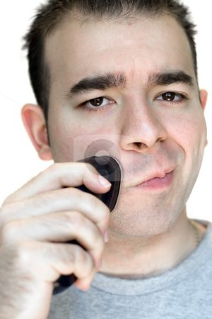 Young Man Shaving stock photo, A closeup of a young man shaving his beard off with an electric shaver. by Todd Arena