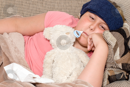 Sick stock photo, Closeup view of a young girl with a thermometer in her mouth and a damp cool cloth on her forehead, indicating she has a fever by Richard Nelson