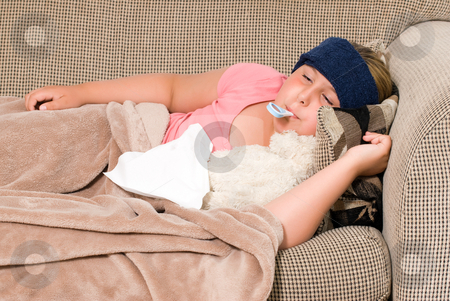 Sick Kid stock photo, A young girl with a fever is lying on the sofa waiting to feel better by Richard Nelson