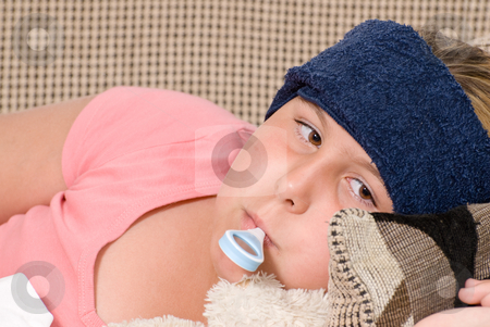 Fever stock photo, Closeup view of a young girl with a thermometer in her mouth and a damp cool cloth on her forehead, indicating she has a fever by Richard Nelson