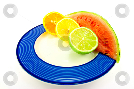 Watermelon with Citrus Halves stock photo, Slice of red juicy watermelon with lemon, lime and orange halves on a blue plate with a white background by Keith Wilson