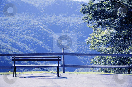 Nature bench stock photo, A lonely bench set upon a backdrop of mountains. by Kristen Wood