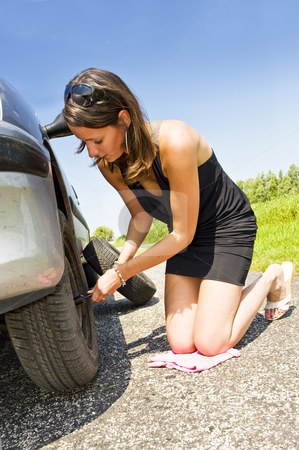 Changing a tire stock photo, Young woman kneeling, changing the front tire of her car by Corepics VOF