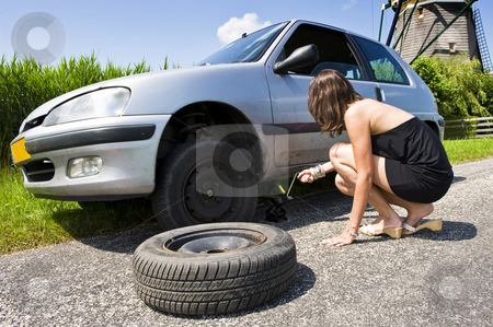 Jacking stock photo, Young woman jacking up her car to change a flat tire with a spare one by Corepics VOF