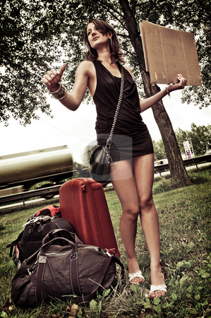 Hitch hiking stock photo, Young woman with a lot of luggage, trying to get a ride by hitchiking. by Corepics VOF