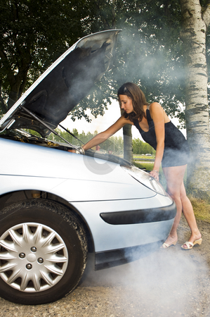 Car trouble stock photo, A young woman, looking under the hood of her car to see what's wrong with her engine by Corepics VOF