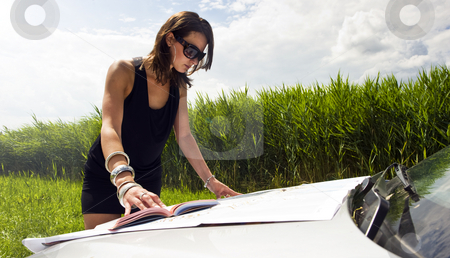 Directions stock photo, Young woman, studying a map and a guide book on the hood of her car on a bright summer day by Corepics VOF