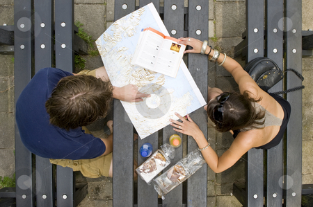 Planning a trip stock photo, Young couple planning a trip on a map, with a guide book on a picknick table, with pastries and soda bottles by Corepics VOF