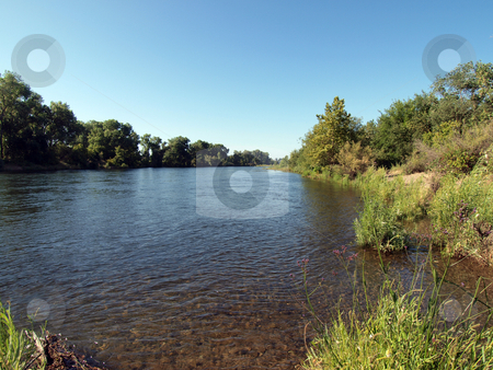 View up river from banks blue sky summer day stock photo, View of river with green trees on banks and blue sky by Jeff Cleveland