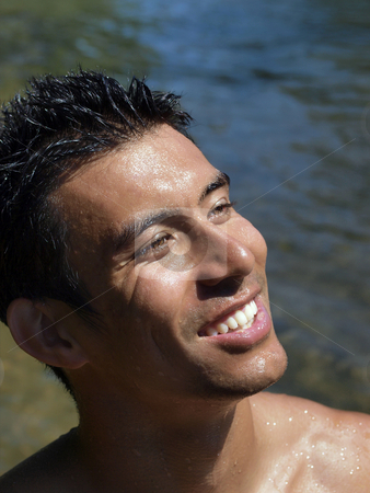 Smiling young man dripping with water at river stock photo, Outdoor portrait of young man dripping wet at river by Jeff Cleveland