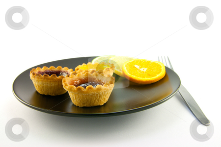 Jam Tarts with Citrus Slices and Fork stock photo, Red and yellow small jam tarts with slices of lemon, lime, and orange on a black plate with a fork on a white background by Keith Wilson