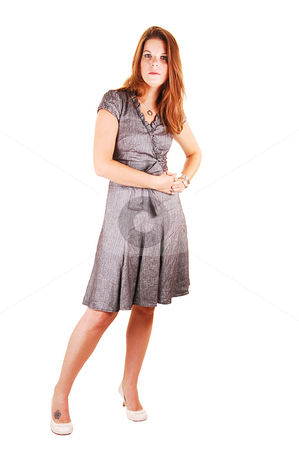 Pretty girl in gray dress. stock photo, Young lovely girl in a gray dress with red lips and high heels standing in the studio for white background. by Horst Petzold