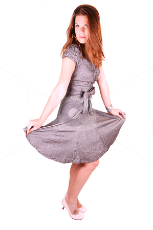 Pretty girl in gray dress. stock photo, Young lovely girl in a gray dress dancing in the studio for white background. by Horst Petzold