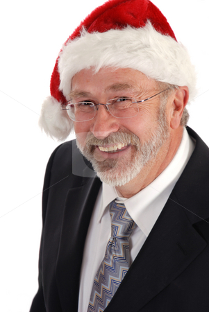 Smiling Businessman Christmas hat stock photo, Senior Businessman wearing Santa claus hat. by Damien Richard