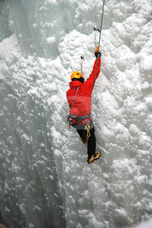 Ice Climber stock photo, An Ice Climber going up a frozen waterfall. by Damien Richard