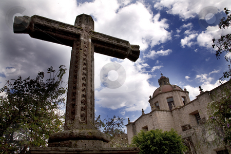 La Guadalupita Church Morelia Mexico with Stone Cross stock photo, Stone Cross Outside of La Guadalupita Church Morelia Mexico with Blue Skies and Fluffy Clouds by William Perry