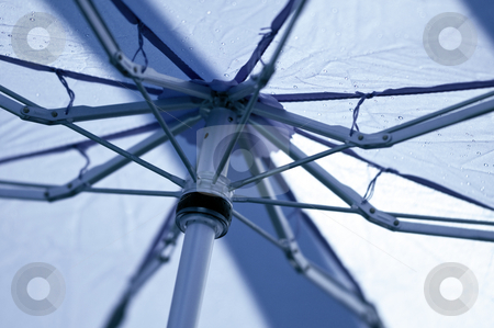 Blue umbrella stock photo, A blue umbrella with raindrops. by Kristen Wood
